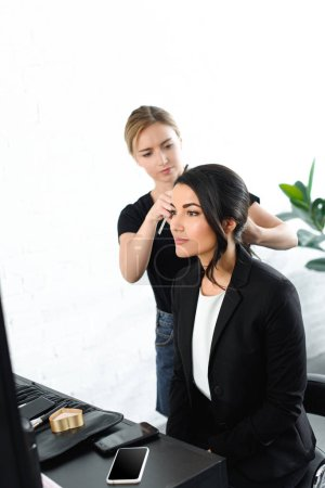 selective focus of hairstylist doing hairstyle for businesswoman in suit
