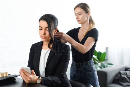 focused hairstylist doing hairstyle while businesswoman in suit using smartphone