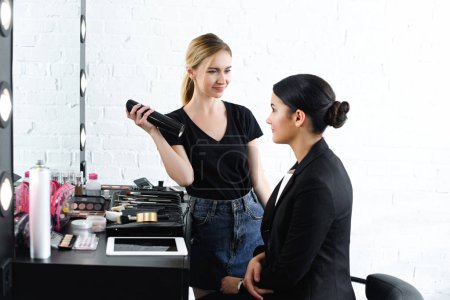 smiling hairstylist with hair spray and businesswoman in black suit