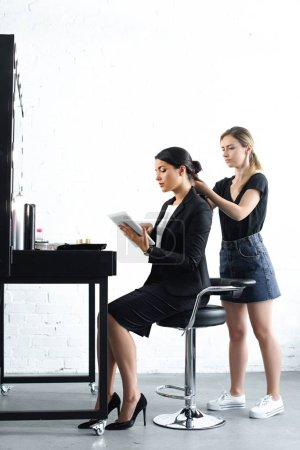 side view of hairstylist doing hairstyle while businesswoman in suit using digital tablet