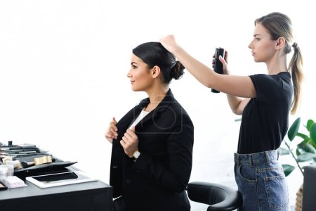 side view of businesswoman getting hairstyle fixated with hair spray by hairstylist