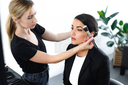 young businesswoman getting makeup done by makeup artist