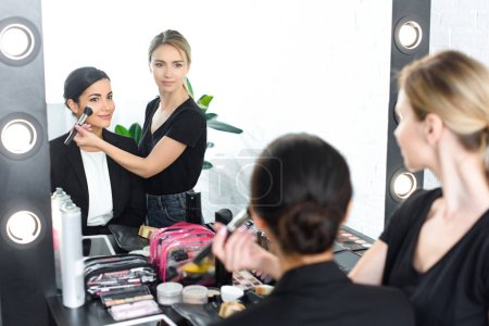 young smiling businesswoman getting makeup done by makeup artist