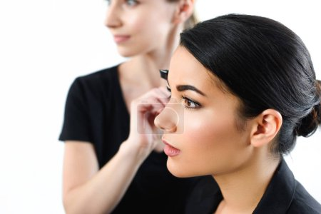selective focus of young businesswoman getting makeup done by makeup artist