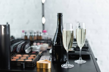 close up view of bottle and glasses of champagne on tabletop with cosmetics for makeup
