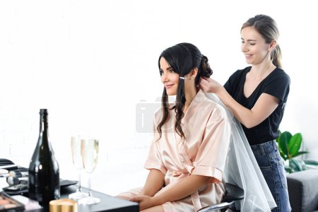 smiling hairstylist fixating veil on brides hair