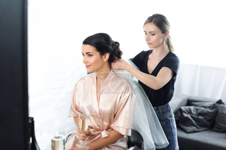 side view of focused hairstylist fixating veil on brides hair