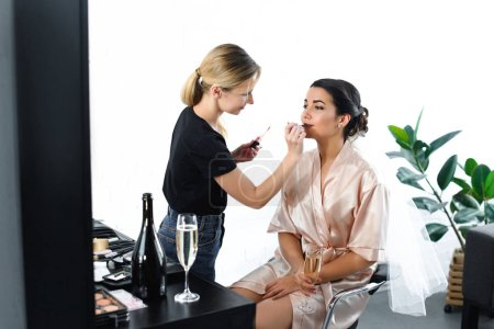 side view of makeup artist applying lipstick on brides lips