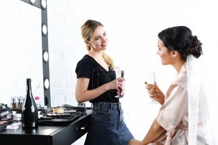side view of smiling makeup artist and bride in silk bathrobe with glasses of champagne