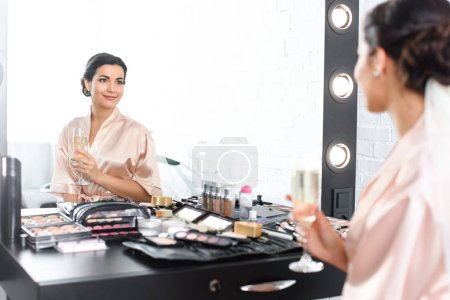 mirror reflection of smiling bride in silk bathrobe and veil with glass of champagne sitting at tabletop with cosmetics