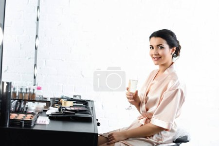 side view of smiling bride in silk bathrobe and veil with glass of champagne sitting at tabletop with cosmetics