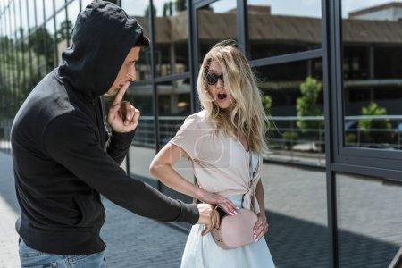 Photo pour Symbole de silence voleur montrant tout en smartphone de vols à la tire du sac d'une femme choquée - image libre de droit