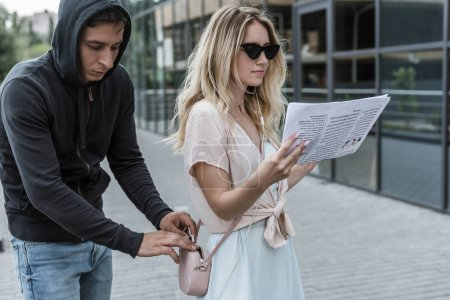 woman reading newspaper while robber pickpocketing smartphone from her bag