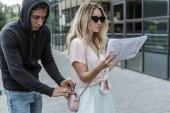 Femme lisant le journal tout en smartphone de voleur vol à la tire de son sac