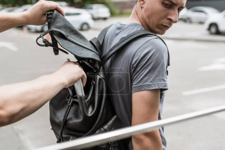 robbery pickpocketing laptop from mans backpack on street
