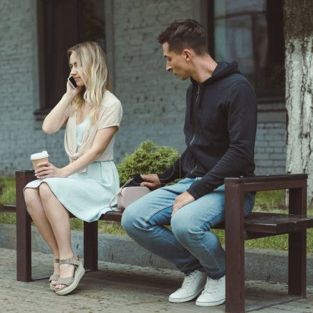 man pickpocketing wallet from bag of woman with coffee talking on smartphone on bench in park