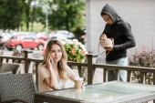 man stealing bag from table on restaurant terrace while woman talking on smartphone