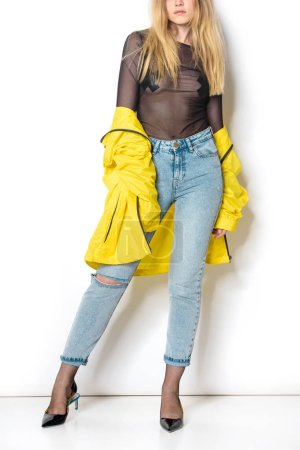cropped shot of young woman in transparent shirt and yellow jacket on white