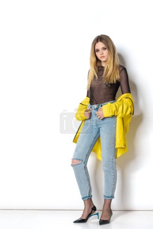 beautiful young woman in transparent shirt and yellow jacket on white