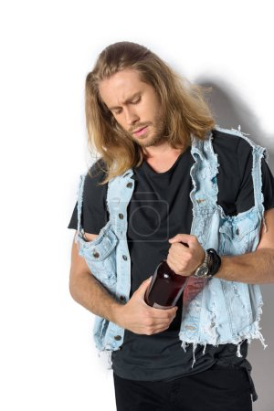 attractive young man in denim vest opening bottle of rum on white