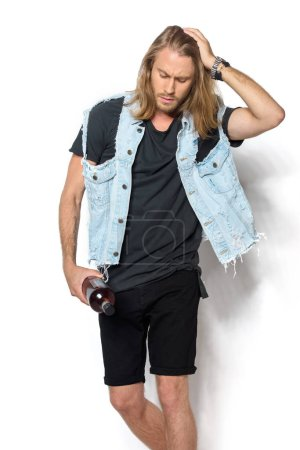 handsome young man in denim vest with bottle of rum on white