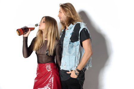 stylish young addicted couple with drinking rum on white