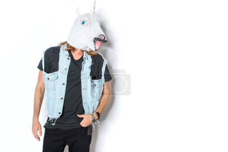 man in unicorn mask and denim vest standing on white
