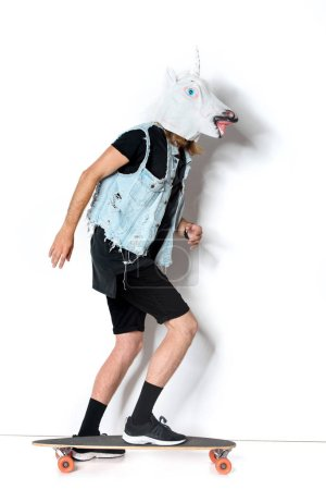 side view of man in unicorn mask and denim vest riding skateboard on white