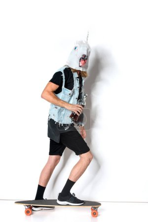 side view of man in unicorn mask and denim vest with bottle of rum riding skateboard on white