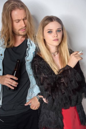 young stylish addicted couple with beer and cigarette on white