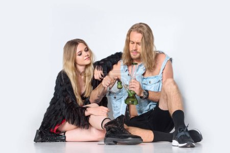 high couple sitting on floor and smoking water pipe of cannabis on white