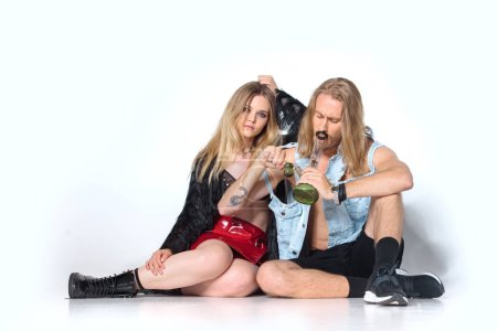 young addicted couple sitting on floor and smoking water pipe of cannabis on white