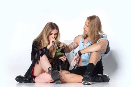 Photo pour Jeune couple accro, assis sur le plancher et la conduite d'eau de fumer du cannabis sur le blanc - image libre de droit