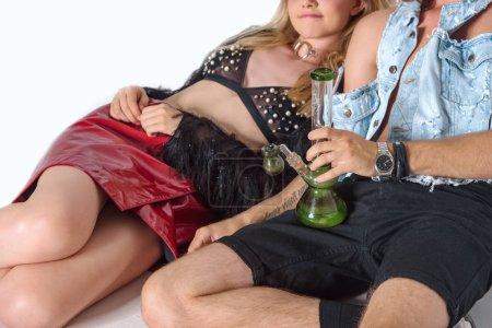 Photo pour Jeune couple élevé, assis sur le sol avec la pipe à eau du cannabis sur blanc - image libre de droit