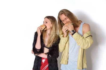 hungry young couple eating tasty burgers on white