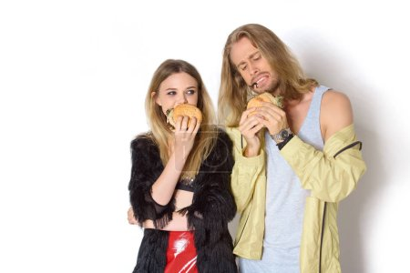 hungry stylish young couple eating tasty burgers on white