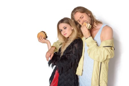 stylish young couple eating delicious burgers on white