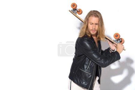 Photo pour Séduisante jeune homme en veste de cuir avec longboard sur blanc - image libre de droit