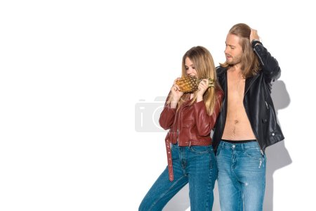 stylish young couple in leather jackets with pineapple standing together on white