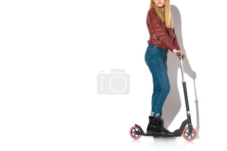 cropped shot of stylish young woman in leather jacket with scooter on white