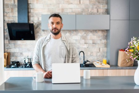 portrait of bearded man standing at counter with laptop and cups of coffee and looking at camera in kitchen