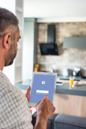 selective focus of man using digital tablet with facebook logo on screen in kitchen