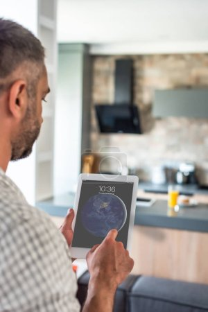 selective focus of man using digital tablet in hands in kitchen