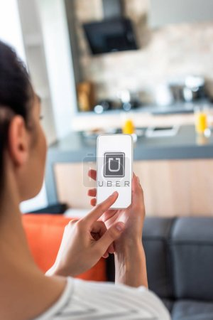 selective focus of woman using smartphone with uber logo on screen in kitchen