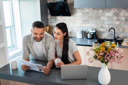 portrait of smiling married couple reading newspaper together at counter with laptop in kitchen