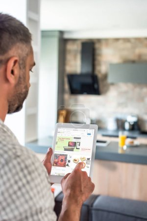 selective focus of man using digital tablet with ebay website on screen in kitchen