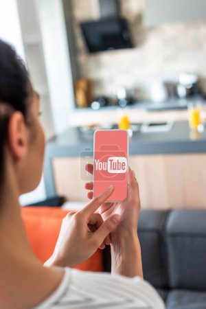 selective focus of woman using smartphone with youtube logo on screen in kitchen