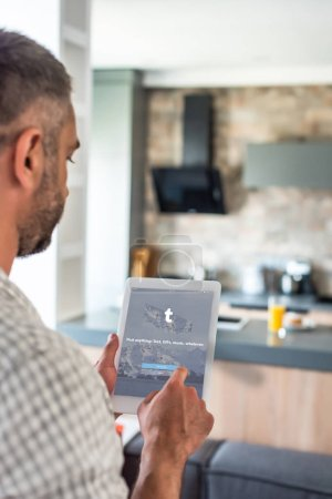 selective focus of man using digital tablet with twitter logo on screen in kitchen