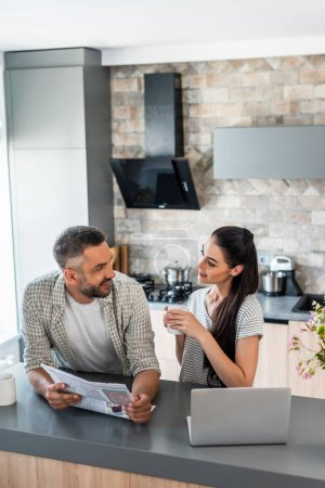 portrait of married couple with newspaper and cup of coffee standing at counter with laptop in kitchen