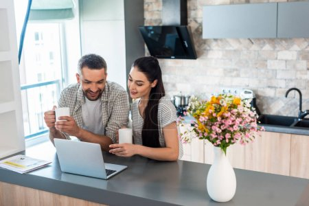 smiling married couple looking at laptop screen together at counter in kitchen